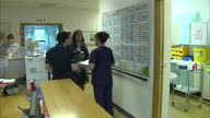 Interior shots of nursing staff discussing shift rota arrangements making telephone calls and checking paperwork at Milton Keynes University...