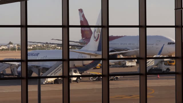 Interior shots of passengers waiting in Sharm el Sheikh's airport departure lounge and planes parked on the taxiway visible outside on November 05...