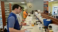 Interior shots of pharmacists working behind the counter at Princeton Pharmacy in Princeton Illinois Pharmacists work on putting together orders for...