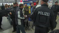 Interior shots of police on station platform meeting refugees as they arrive in Munich Germany checking bags and documents and gathering them...