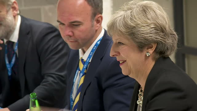Interior shots of Prime Minister Theresa May and German Chancellor Angela Merkel sat around a table for talks on global security on 29 September 2017...