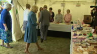 Interior shots of Prince Charles and Camilla Duchess of Cornwall speaking to locals and browsing children's toys and baked goods for sale at a stall...