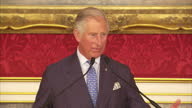interior shots of Prince Charles Prince of Wales entering room and sit down and shots of him walking up to podium and give speech at St James' Palace...