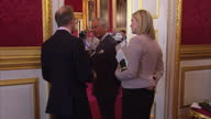 interior shots of Prince Charles Prince of Wales talking to guests whilst drinking a cup of tea at St James' Palace on May 13 2015 in London England