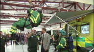 Interior shots of Prince Harry joking with a group of paramedics demonstrating rescue equipment spinning one of the paramedics dangling from the...
