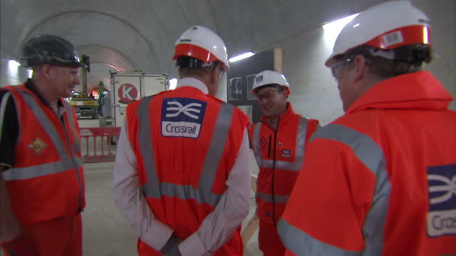 Interior shots of Prince Philip Duke of Edinburgh wearing a hi vis jacket and hard hat visiting and being shown round Crossrail Farringdon station...