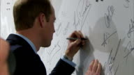 interior shots of Prince William Duke of Cambridge signing a wall at St George's Park and close up shots of his and Kelly Holmes' signatures on May...