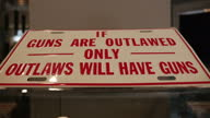 Interior shots of progun lobby slogans in a gun shop including a metal plaque reading 'If guns are outlawed only outlaws will have guns' and 'Guns...