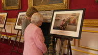 Interior shots of Queen Elizabeth II and Prince Charles looking at various pictures and paintings at a reception to bring together the community of...