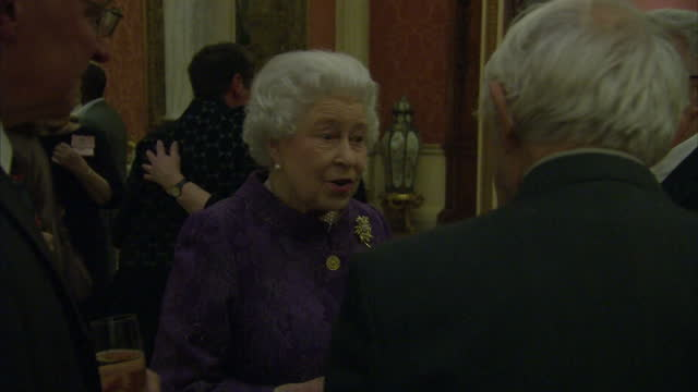 Interior shots of Queen Elizabeth II meeting assembled poets and guests at a reception for contemporary British poetry at Buckingham Palace...