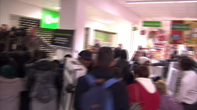 Interior shots of staff opening the doors of an ASDA supermarket and crowds of Black Friday shoppers piling in and grabbing at a pile of flatscreen...