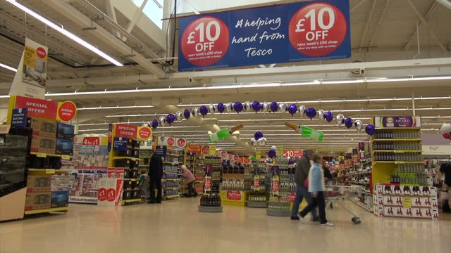 Interior shots of staff packing on line orders customers browsing the aisles in Tesco Extra and exterior shots of the Tesco Extra entrance in...