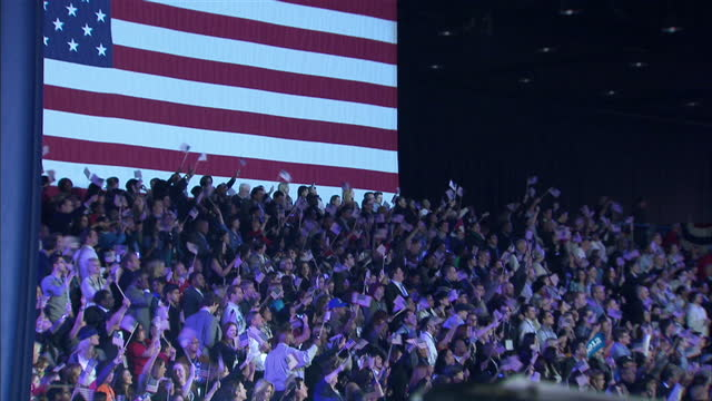 Interior shots of supporters waving flags and celebrating as results are announced at the ObamaBiden election night rally at McCormick Place in...