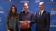 Interior shots of the Duke and Duchess of Cambridge posing with NBA player Dikembe Mutombo and NBA Commissioner Adam Silver to promote the new...