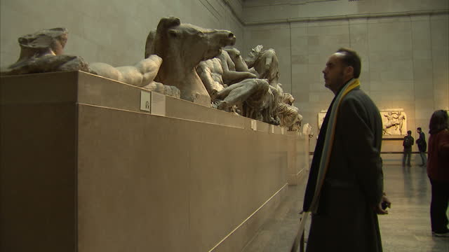 Interior shots of tourists viewing parts of the Parthenon friezes and pediment sculptures also known as the Elgin Marbles on display in the British...