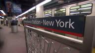 Interior shots of travellers walking along a platform at Pennsylvania Station including a shot of a Pennsylvania Station New York sign on the...
