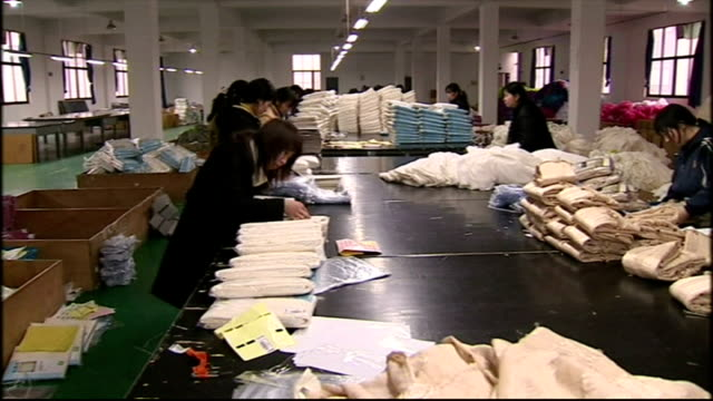 Interior shots of women working in a textile factory making clothes including a shot of a 'Made in China' label on a product destined for Wal Mart on...