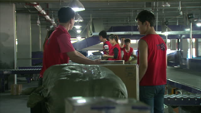 Interior shots of workers in the YTO Express parcel distribution depot sorting through parcels on various conveyor belts on September 16 2014 in...