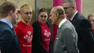 Interior shots Prince Philip shaking hands and meeting volunteers from the Prince Trust