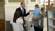Interior shots Prince William talk to family holding children