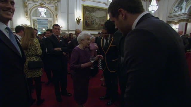 Interior shots Queen Elizabeth II talking with guests at Rugby World Cup reception at Buckingham Palace on October 12 2015 in London England