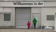 Interior shots refugees at relief centre in Munich Exterior shots entrance makeshift migrant relief shelter signage 'WILLKOMMEN IN DER' on September...