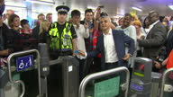Interior shots Sadiq Khan London Mayor swipes through ticket barrier talks to London Underground staff and heads down to platform on escalator on...