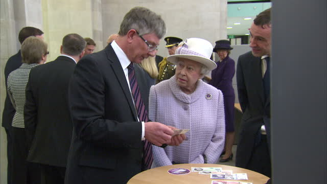 Interior shots the Queen looks at new bank notes Interior shots Prince Philip chats with staff Interior shots the Queen Prince Philip tour room full...