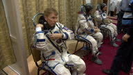 Interior shots Tim Peake putting on space suit in changing room lots of buckles and zips