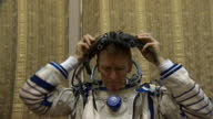 Interior shots Tim Peake sat in changing room suiting up putting on space suit ahead of training exercise