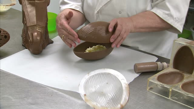 Interior shots worker making chocolate Easter Eggs removing chocolate eggs from moulds filling with white chocolate buttons and sealing shut on...
