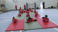 Interior shots young primary school children stretching and doing basic gymnastics on gym matts all wearing Beth Weddle Academy tshirts Beth Tweddle...