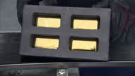 Interior shows gold mould box after being in furnace gloved hand lifts lid to reveal gold brick bullion in moulds