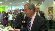 Interior shows Nigel Farage at Ukip conference lobby hall leader goes to stall and speaks to vendor at Doncaster Racecourse on September 29 2014 in...