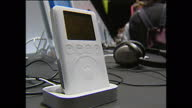 Interior stock shots of people using Apple computers in showroom with iPod attachments looking at iTunes website first iPod MP3 players at launch of...
