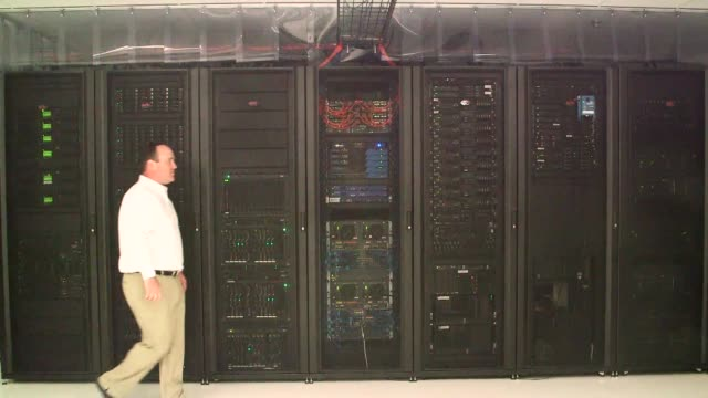 Interiors of a Cavern Technologies Server Room in Lenexa Kansas A while male technician walks past a row of servers decks and towers Close up shots...