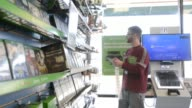 Interiors of an employee stocking the shelves of a GameStop store in Peru Illinois US A young white male employee places price tags on video games...