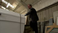 Interiors of UKIP leader Nigel Farage in boat factory including him climbing a ladder on February 12 2015 in Canvey Island England