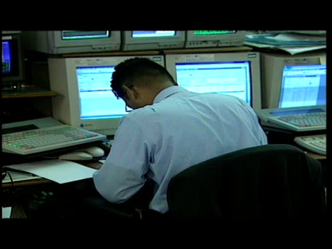 Interiors var of traders sitting in front of computer monitors trading on phones