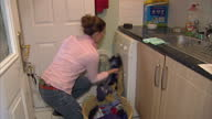 Internal shots of a woman loading a washing machine with laundry switching the washing machine on and clothes going through a wash cycle in the...