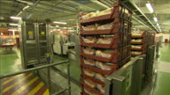 Internal shots of packaged loaves of Warburtons bread being placed on conveyor belt by robotic arm packets of bread being sealed and crates of...