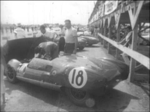 high angle establishing LSs downtown Havana skyline TLS activity in pits racetrack MS/TLSs mechanics working on Maserati Tipo 61 'Birdcage' sports...