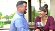Interracial couple drinking wine on restaurant patio
