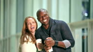 Interracial couple holding coffee cups, walk to camera