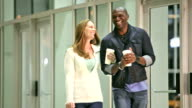 Interracial couple on a date night, walking by building