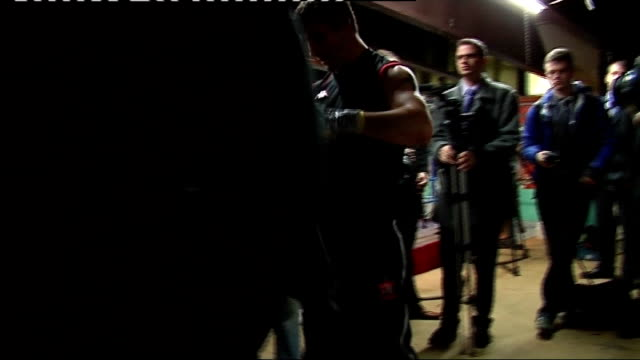 Interviews with Joe Calzaghe and Enzo Calzaghe Calzaghe using punchbag and talking to press / Calzaghe talking to others in boxing ring