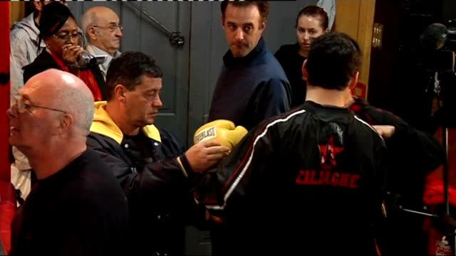 Interviews with Joe Calzaghe and Enzo Calzaghe More of Calzaghe workin out in front of mirror press and other officials / Calzaghe talking to others...