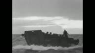 VS invasion fleet moving toward France / VS landing barges in choppy water / men fire mortars from deck of landing storage tank / black smoke water...