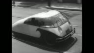 Inventor of bug car Dr Calvin Blackman Bridges stands smiling for camera in San Francisco California / small insect shaped car on road / drives past...