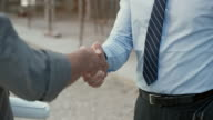 Investor and architect shaking hands outside at the construction site